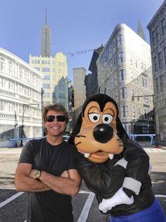 on Bon Jovi poses with Disney character Goofy on the New York Street set at Disney's Hollywood Studios theme park in Lake Buena Vista, Florida.