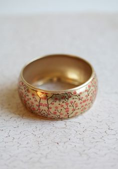 """Sweet Blossoms Bangle 12.99 at shopruche.com. This golden bangle is finished with a delicate cherry blossoms print.  2.75"""" diameter"""