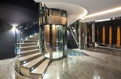 Trendy: A spiral staircase curves around a glass lift shaft giving residents options over how to get around the house