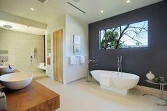 modèle de salle de bain avec baignoire-îlot ovale, plan vasque en bois et mur graphite