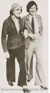 Two women from the 1920's both in mannish suits including wide-leg trousers, a tie, the jacket, and hats.