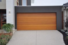 Emilio Modern Style Custom Wood Garage Door EMILIO by Pena. The Pena Modern Wood Doors Collection incorporates handcrafted wood to enhance its classic appe Garage Door Cost, Cedar Garage Door, Unique Garage Doors, Contemporary Garage Doors, Garage Doors Prices, Garage Door Panels, Custom Garage Doors, Carriage Garage Doors, Wooden Garage Doors