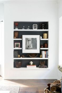 A picture hanging on the front of a bookcase adds a touch of the unexpected. In this example from Carla Lane Interiors, painting the back of the bookcase black helps the art to really stand out. I also like how the symmetrical composition makes the art the star of the show, almost as if the whole bookcase is a really large frame. Obviously, if you're going to do this, the things you put on the shelf behind the picture frame should be things you don't need to access very often.