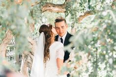 Gorgeous wedding photo of the bride and groom through the trees