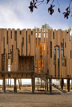 <p>The east wall displays an abstraction of solids and voids that mimics the solids and voids of the forest wall, here rendered in staggered vertical board rainscreen siding, sometimes positioned over solid wall and sometimes lapping over glazing. <br><small>© Peter Aaron/OTTO</small></p>