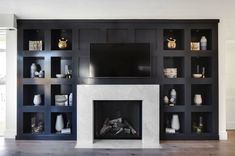 Stunning black built-in niche shelves surround a white marble fireplace mantel with interior black herringbone tiles. Stunning black built-in niche shelves surround a white marble fireplace mantel with interior black herringbone tiles. Black Fireplace Mantels, Marble Fireplace Mantel, Fireplace Built Ins, Marble Fireplaces, Fireplace Surrounds, Fireplace Design, Fireplace Shelves, Stone Fireplaces, Black Fireplace Surround