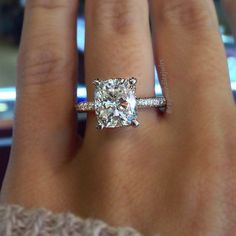 Cushion Cut solitaire engagement ring on a thin diamond band