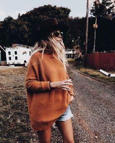 Oversized orange knit sweater with denim shorts.