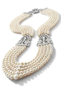 An Impressive Natural Pearl and Diamond Necklace, with 1930s Art Deco diamond plaques. Composed of five rows of graduated natural pearls measuring from approximately 11.30 to 5.00mm, the open work geometric plaques and clasp set with variously shaped diamonds. #diamondnecklaces