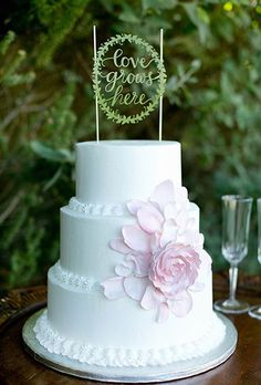 "A laser-cut ""Love Grows Here"" wedding cake topper 