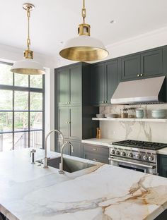 Architect Elizabeth Roberts splurged on Calacatta Gold marble countertops, gold-lined pendants and custom cabinets in a gorgeous grey-green hue in this kitchen.   Photographer: Dustin Aksland