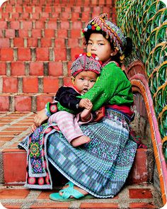 A young girl and her little sister in traditional dress, sitting, begging for money on the stairs leading up to a popular temple tourists frequent to grab a panoramic view of Chiang Mai and its surrounding area.     Thailand adventure.   The land of smiles