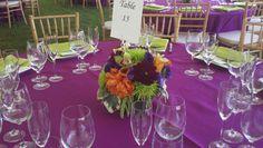 Bright Summer wedding centerpiece. Features dahlias, roses, green cymbidium orchids, mums. Petal Town Flowers