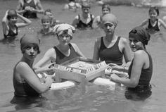 A group of c. 1920s women playing a game of floating Mah Jongg at the beach.