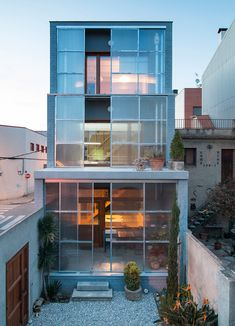 Sliding polycarbonate screens are set in front of the windows covering the stepped facade of this house in Barcelona by Spanish studio H Arquitectes