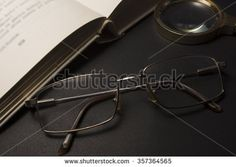Ophthalmologist concept with book, eyeglasses and magnifying glass. High resolution image. - stock photo