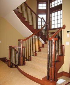 Custom-built flared stairways featuring rustically elegant wrought iron spindles