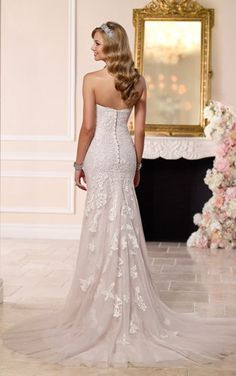You'll love how the strapless sweetheart neckline with lace detailing of this tulle Stella York wedding dress frames your face, while the bodice hugs your every curve. Choose from a corset closure or a zipper closure under fabric-covered buttons.