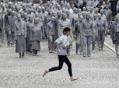 """Une femme traverse la rue à Hambourg devant la performance d'un collectif d'artistes """"1.000 Gestalten"""" qui manifeste, mercredi 5 juillet, contre le G20 qui va se tenir dans la ville allemande ce week-end. Au total, les organisateurs attendent sur plusieurs jours plus de 100.000 manifestants anti-G20 à Hambourg, dont plusieurs milliers d'extrémistes de gauche prêts à en découdre selon la police.  Matthias Schrader/AP/SIPA"""