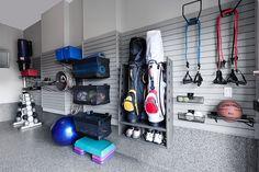 Sports equipment neatly organized on a garage wall using a slatwall system.