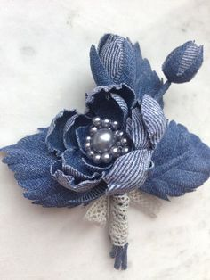 This flowers has been handmade using layers of denim with each petal being hand cut, pressed and shaped using traditional millinery tools and