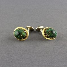 This is a fantastic pair of Egyptian Revival natural scarab beetle cufflinks. The Victorian cufflinks have a genuine leaf beetle, an iridescent insect that has an oval, textured green body. The beetle is prong set in a gold tone cufflink with a border that has a subtle scroll design. There is a curved shank that is attached to a solid rounded oval foot instead of a moveable toggle.  The cufflinks were made around the turn of the last century.  A smaller size, they measure 3/4 inch wide, ...