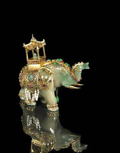 A jadeite jade and gem-set elephant with the carved emerald face, riding in a gold howdah, accentuated with various shapes of emeralds, rubies, sapphires and freshwater cultured pearls, with wooden stand; detailed in fourteen karat gold.
