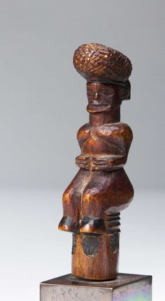 """Lwena, Angola; H: 3 3/4"""" The tiny figurine probably once the top of a snuff box, the figure sitting with typical high coif and classically carved face, the body well rendered with arms wrapped about the torso and wide hips and legs. The bottom of the stopper with pyro engraved circles."""