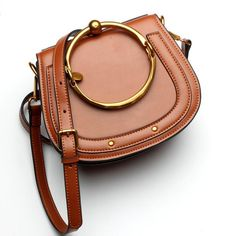 · This wristlet sling bag comes with a very attractive brass buckle design · The golden color of the buckle makes you instantaneously stand-apart · The color of the belt is same as the color of the bag and high in quality · The adjustable cross-body strap is another prominent feature of this ama