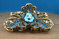 This vintage, brass hair clip features an ornate floral design with turquoise gemstones, aqua rhinestones, and gold-colored brass. Turquoise Hair, Turquoise Gemstone, Turquoise Bracelet, Petal Floral, Hair Clips, Floral Design, Aqua, Hair Accessories