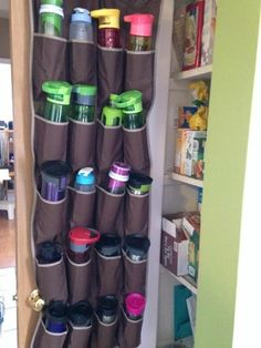 Water bottle storage using an over the door shoe rack on the pantry door {featured on Home Storage Solutions 101}
