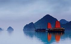 Halong Bay in mist with Junk in the foreground.