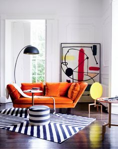 Bold furniture does all the work in this living room – we adore this Flexform orange sofa. Image: Livingetc