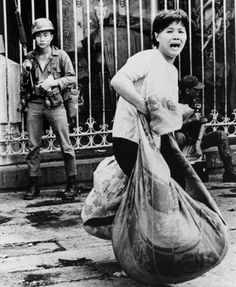 Screaming refugee woman flees her home with bundled possessions during Viet Cong attack on Saigon's Chinatown during the Mini Tet Offensive in Vietnam in June 1968. © Nik Wheeler