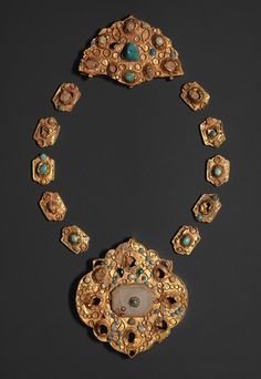 Elements from a necklace, probably 14th century  Iran  Gold sheet, chased and inset with turquoise, gray chalcedony, glass; large medallion: 2 7/8 x 2 3/4 in. (7.3 x 7 cm), half-medallion: 1 3/4 x 2 3/4 in. (4.4 x 7 cm), cartouches: 3/4 x 1/2 in. (1.9 x 1.3 cm)  Rogers Fund, 1989 (1989.87a–l)