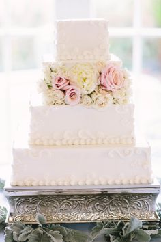 Square butter cream wedding cake with Ivory peony, spray roses with mother of pearl blush roses. Dusty miller around the riser