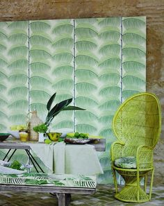 Manila Wallpaper A wallpaper featuring a stylised pattern of upright tropical plants with overlapping leaves in green on ivory.