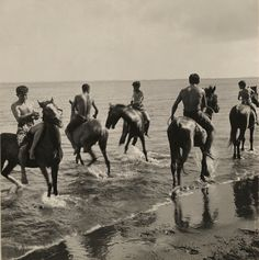 Men on horseback run through the surf in Tahiti, 1922. Photograph by Edward Burton MacDowell, National Geographic Creative