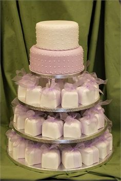 Light purple wedding cake with individually wrapped petit fours. Love the two tiers...top for the anniversary, bottom for the wedding party.