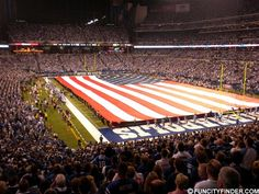 The American flag is unfurled over the field at Lucas Oil Stadium in downtown Indianapolis during the playoffs. Lucas Oil Stadium, Indianapolis Indiana, American Flag, Fields, Skyline, Architecture, City, Arquitetura, Architecture Illustrations