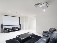 10 Masculine and Sports-Themed Home Theaters: You'll immediately feel like you stepped into the future when entering this modern, black and white home theater. Guests can enjoy lounging in these cozy recliners while taking in the expansive projection screen along the back wall. And with this minimalist look, you won't discover a single distraction. From DIYnetwork.com