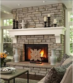 i love the juxtaposed look or rough rocks and smooth white mantel .