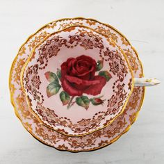 This exquisite vintage teacup and saucer from Paragon features a large red rose design on a pale pink background. Both the cup and saucer have