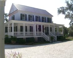 Classic farmhouse colonial with wrap- around porch and standing-seam metal roof