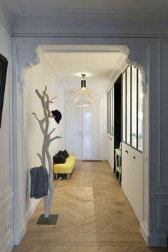hall d'entrée maison avec porte manteaux design arbuste blanc et petit meuble jaune contrastant avec le gris