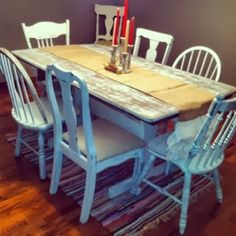 white distressed dining table with mismatched chairs