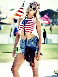 music festival outfit idea: ireland baldwin's American flag crop top, cutoff shorts, fringe crossbody bag, heart-shaped sunglasses and USA flag bandana