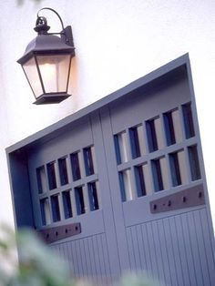 Garage doors with heavy iron strap hardware + oversized lantern | www.bhg.com