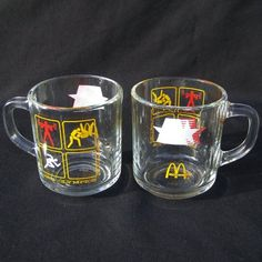 Vintage Set of Two McDonalds 1984 Olympics Glass Mugs - These two collectible Anchor Hocking glass mugs feature 1984 Olympics and McDonald's logos and graphics. They are in good vintage condition with no chips or cracks and some wear. There is an Anchor Hocking makers mark on the bottom. Made in the USA.