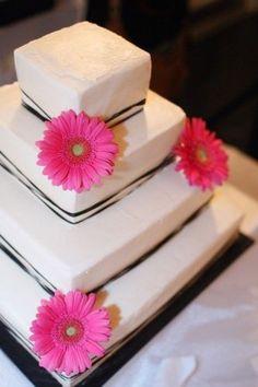 Pink gerbera daisy, black and white wedding cake.